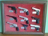 2:Marcos expositores con pistolas en miniatura.